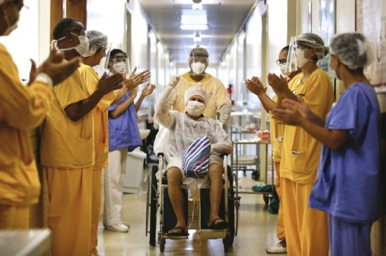 A man raises a fist in the air as he is pushed in a wheelchair down a hospital hallway lined with applauding workers in scrubs