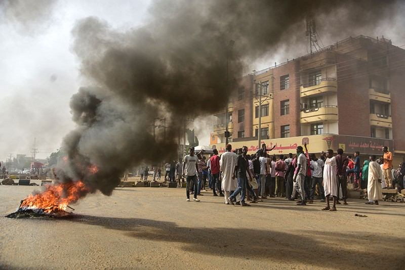 Sudanese protesters walk past burning tyres during a demonstration in Khartoum's twin city of Omdurman on June 3, 2019