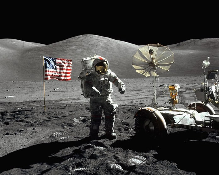 One of the Apollo 17 astronauts stands next to his lunar rover on the surface of the Moon