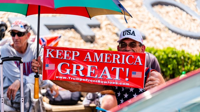 """A person holds a sign that reads """"Keep America Great!"""" outside of the BOK Center ahead of a Trump campaign rally in Tulsa, Okla., June 17, 2020. Trump's resumption of his signature campaign rallies this week is intensifying criticism of his response to the biggest domestic crises of his presidency: the deadly coronavirus pandemic and widening protests over police brutality against Black Americans."""