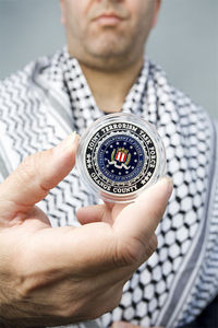Monteilh holds a coin he claims the FBI gave him in recognition of his work