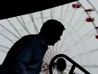 Bill Weld stands in front of a ferris wheel.