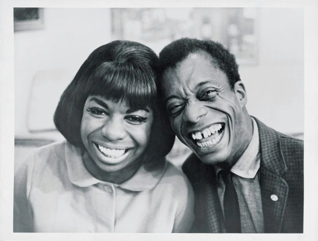 Nina Simone and James Baldwin posing with their heads together and giant smiles on their faces