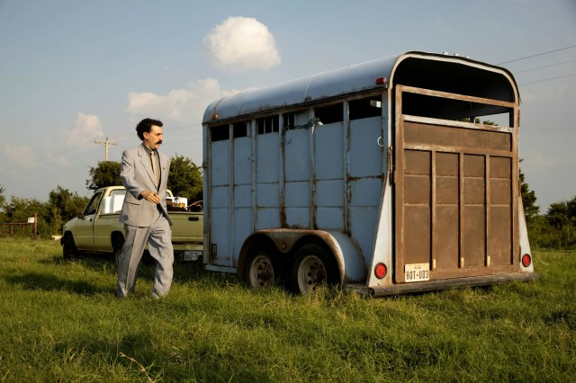Still from Borat Subsequent Moviefilm featuring Sacha Baron Cohen standing next to a trailer