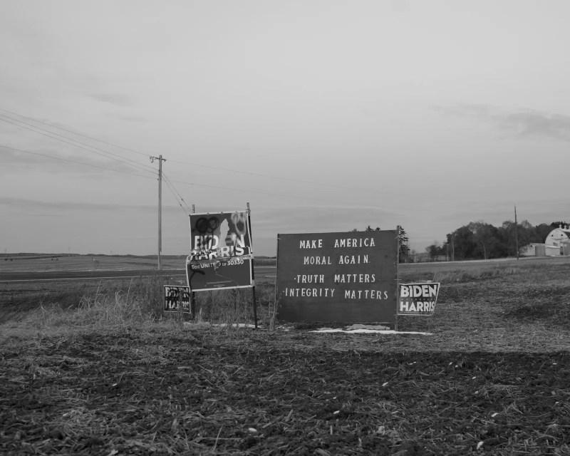 BidenHarris campaign signs stand in a field.