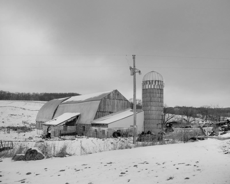 A large dairy farm surrounded by a snowy landscape.