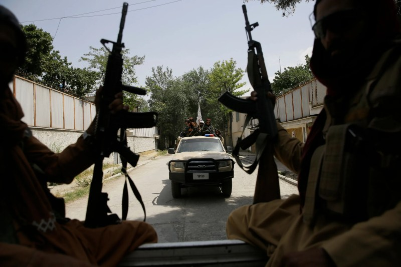 Two silhouetted Taliban fighters sitting in the back of a truck and holding guns with another truck in the background...