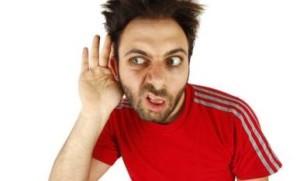 Un ragazzo avvicina la mano all'orecchio per sentire meglio. L'espressione del volto è una smorfia tipica di chi non sente.