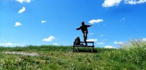 Dario salta da una panchina sulla quale poggia lo zaino. prato verde e cielo blu