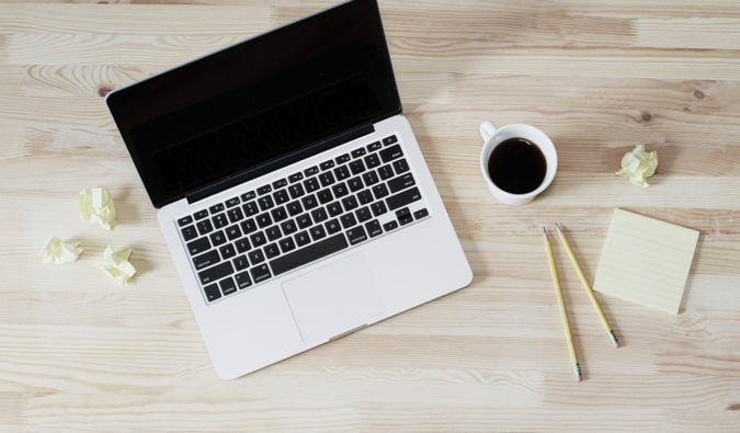 A laptop on a desk beside a cup of black coffee and a notebook