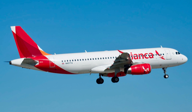 a Avianca flight taking off against a blue sky in Central America