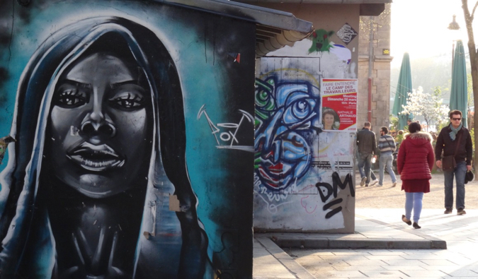 A large street art portrait painted on a wall in Paris, France