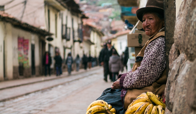 a woman selling bananas sits in the street in Peru