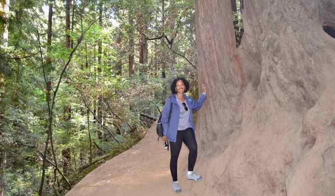 Senitra, a solo black female traveler posing by a huge tree