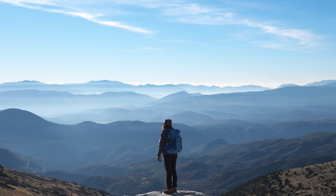 A solo female traveler standing on a mountain