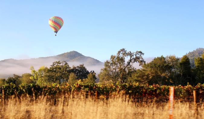 A hot air balloon floating over vineyards in Napa Valley, California