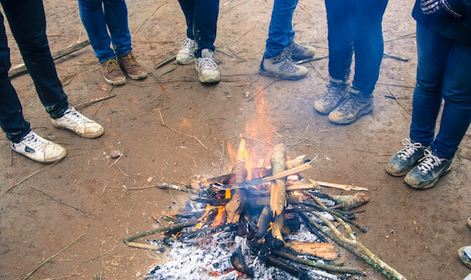 A bunch of solo travelers stand around a campfire