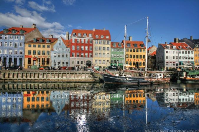 Photo of houses reflecting on the Nyhavn Harbor in Copenhagen, Denmark