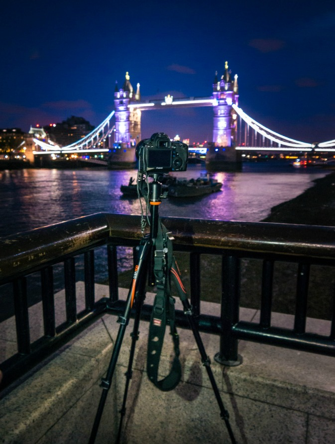 Camera and tripod set up in from of nightcap of Tower Bridge in London