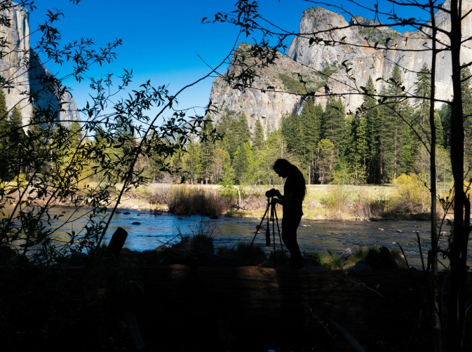 Professional photographer getting ready to shoot a nature travel photo with a blue sky