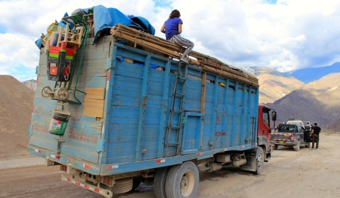 backpacker hitchhiking on top of a truck in Peru