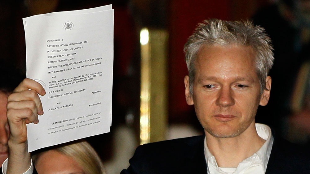 WikiLeaks founder Julian Assange holds up a court document outside London's High Court on Thursday after he was released on bail.