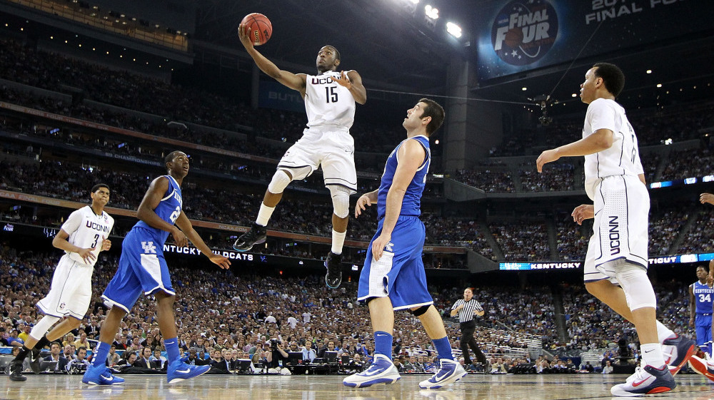 Kemba Walker of the Connecticut Huskies goes to the hoop Saturday past Josh Harrellson and Doron Lamb of the Kentucky Wildcats during the national semifinal game of the NCAA  Men's Basketball Championship in Houston. Connecticut beat Kentucky to advance to the championship game against Butler.