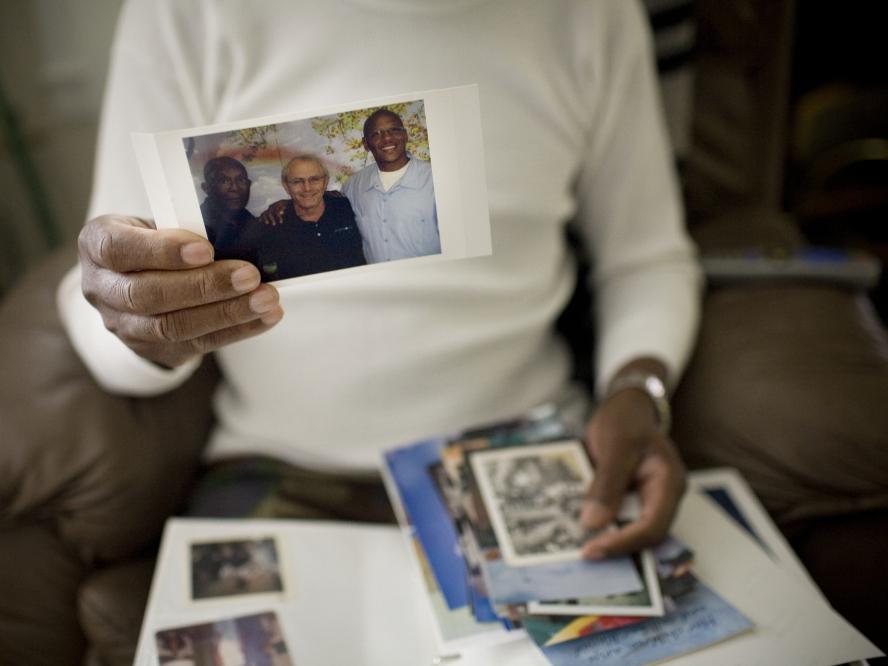 Robert Dixon Sr. holds a photograph of his son, Robert Dixon Jr. (far right), his son's mentor Bob Stuart, and himself (far left).