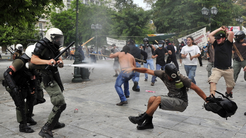 Protesters fight with riot police during massive clashes at the central Athens Syntagma square on Wednesday. Thousands of protesters ringed the Greek Parliament building as the government tried to push through its emergency package inside and a general strike paralyzed the country.