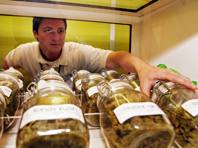 Ryan Cook reaches for a jar of medical marijuana at one of his clinics in Denver on June 24.