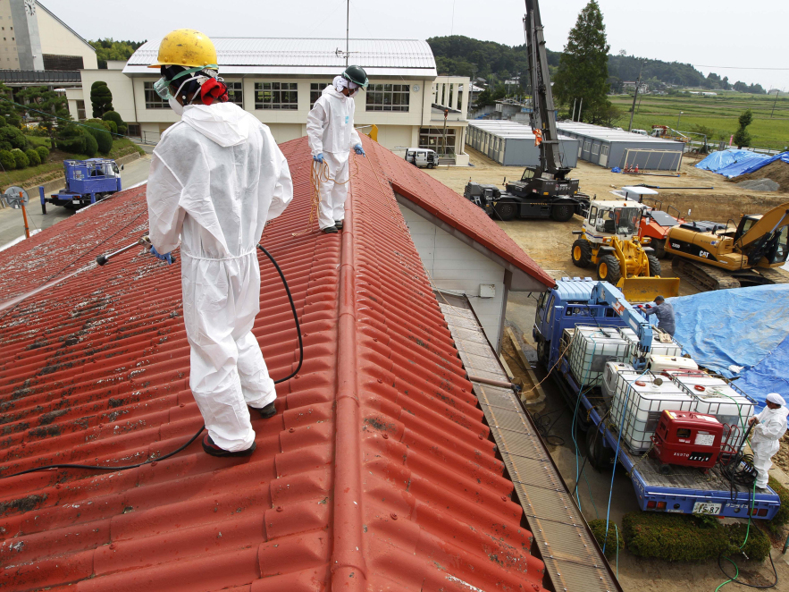 Workers decontaminate radiation from the roof of Yasawa Kindergarten in Minami-Soma, about 12 miles (20 kilometers) away from the tsunami-crippled Fukushima Dai-ichi nuclear facility, in Fukushima prefecture, northeastern Japan, Thursday, Aug. 18, 2011.