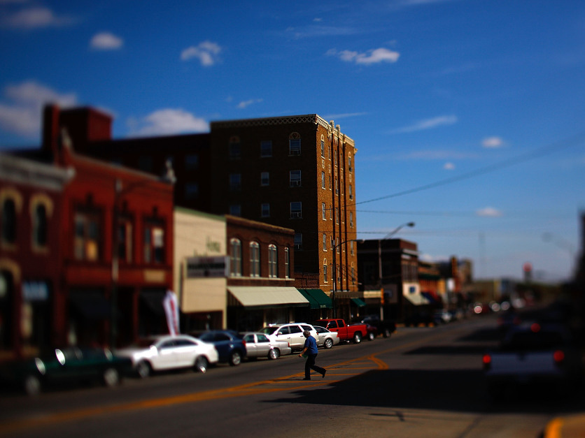 A pedestrian crosses the main street in downtown Chanute, Kan.