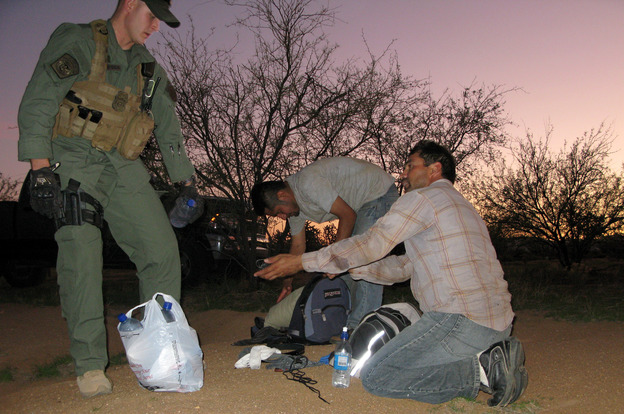 A Border Patrol agent offers water to two men caught after illegally entering the U.S. through the Arizona desert. Roughly 80,000 federal workers have jobs related to immigration enforcement.