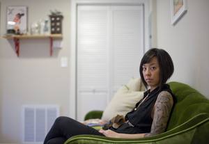 Graphic designer Kaleena Porter sits with her dog, Moby, in the living room of her new home in Northwest D.C.