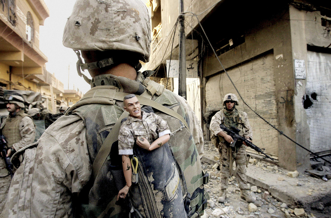 A U.S. Marine of the 1st Division carries a GI Joe mascot as a good luck charm as his unit pushes farther into the western part of Fallujah, Iraq, 2004.