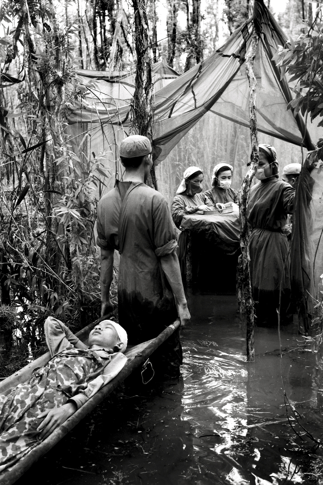 Danh Son Huol, an ethnic Khmer guerrilla, is treated by a medical unit in a swamp in U Minh Forest, Ca Mau peninsula, Vietnam, 1970.