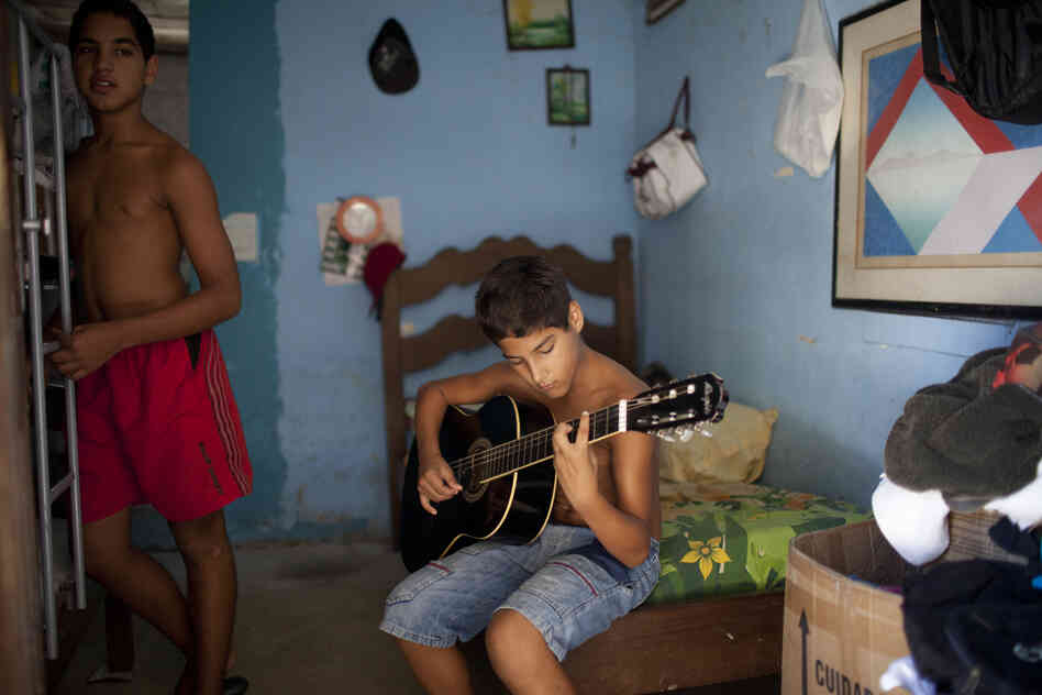 Marcos dos Santos Ribeiro, 11, plays the guitar in his bedroom at home, in Vila Autodromo, where many families have been evicted.