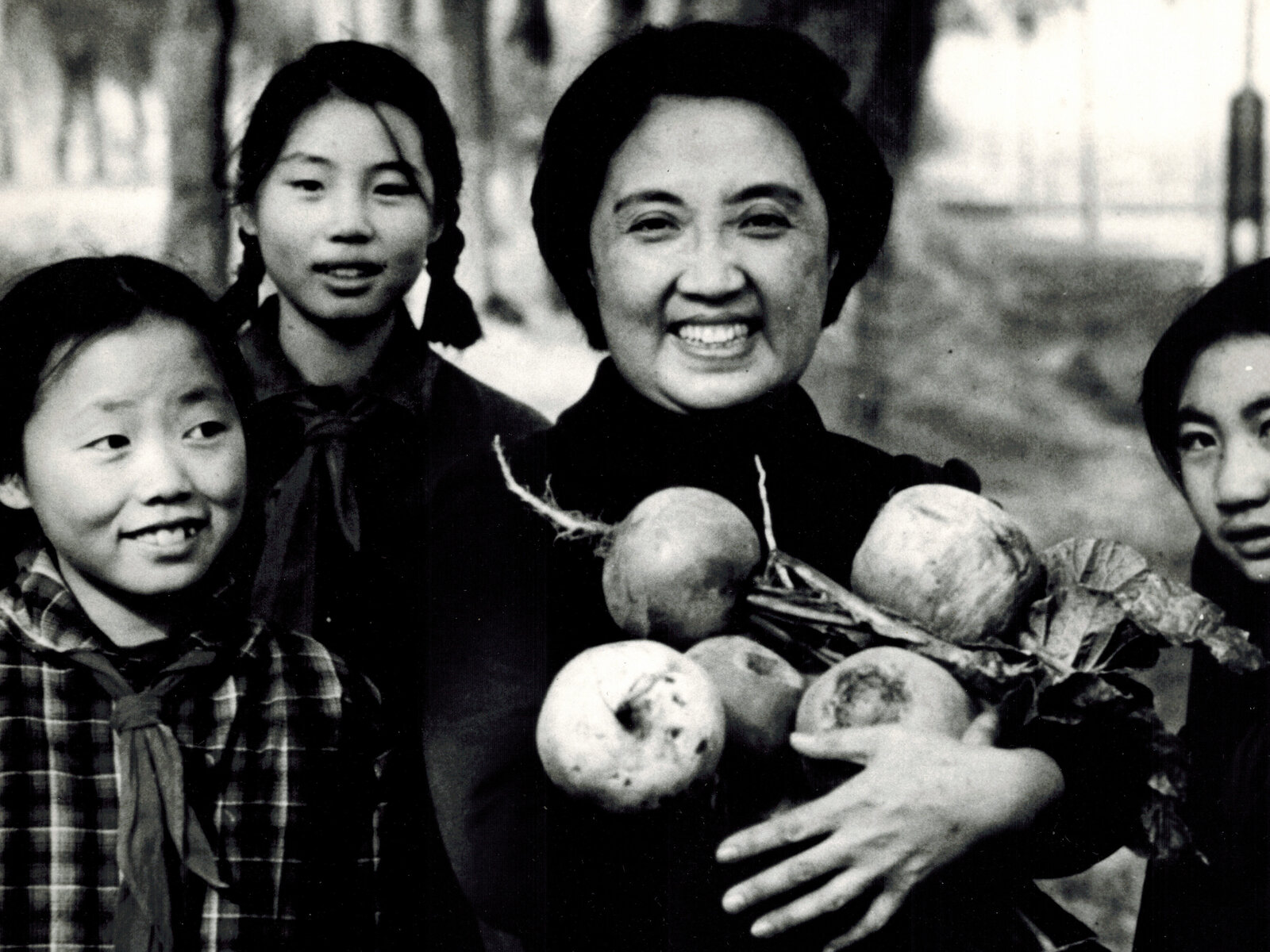 Joyce Chen (center) holds large Chinese radishes picked by middle-school students in Beijing, China, in 1972.