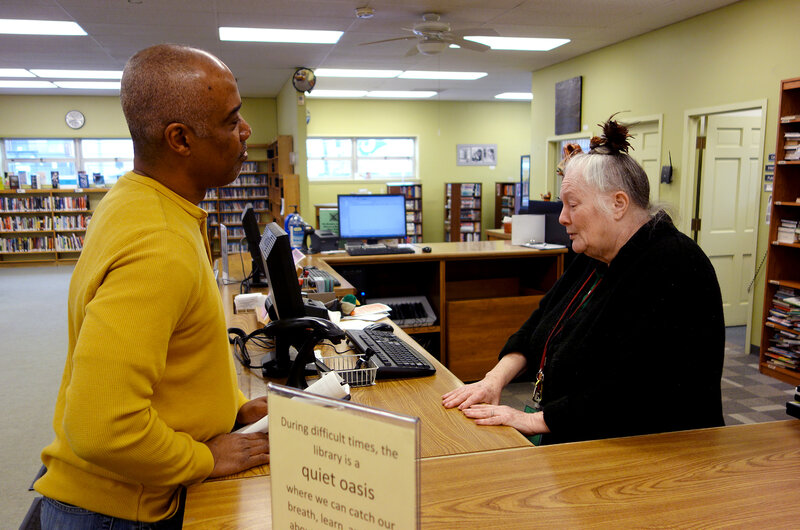 Library volunteer Jeanne Million talks with Ferguson resident Phillip Sampson at the Ferguson Public Library.