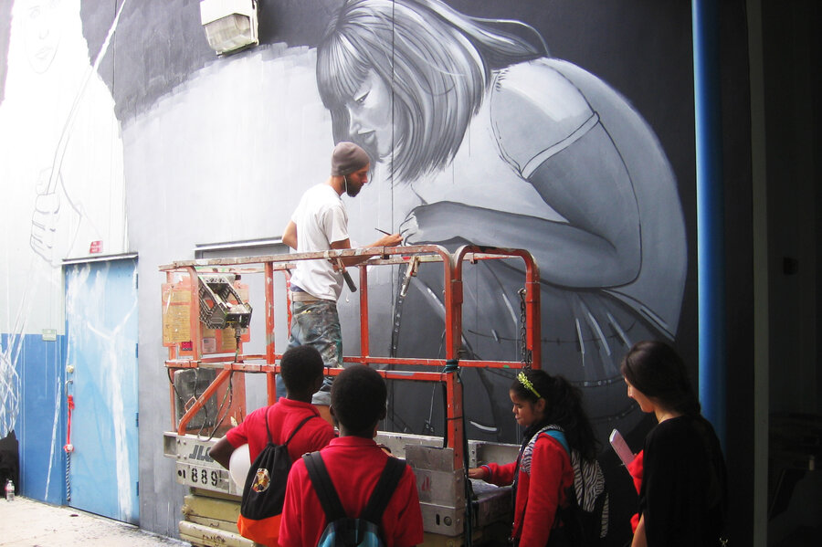 Leza One paints a mural on a wall of Jose de Diego Middle School in Miami's Wynwood neighborhood. It's a project that coincides with the citywide Art Basel fair.