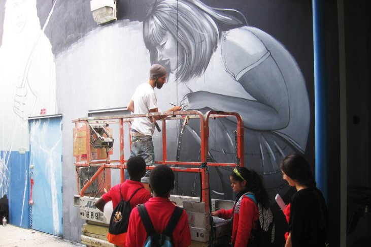 Leza One paints a mural on a wall of Jose de Diego Middle ...</p data-recalc-dims=
