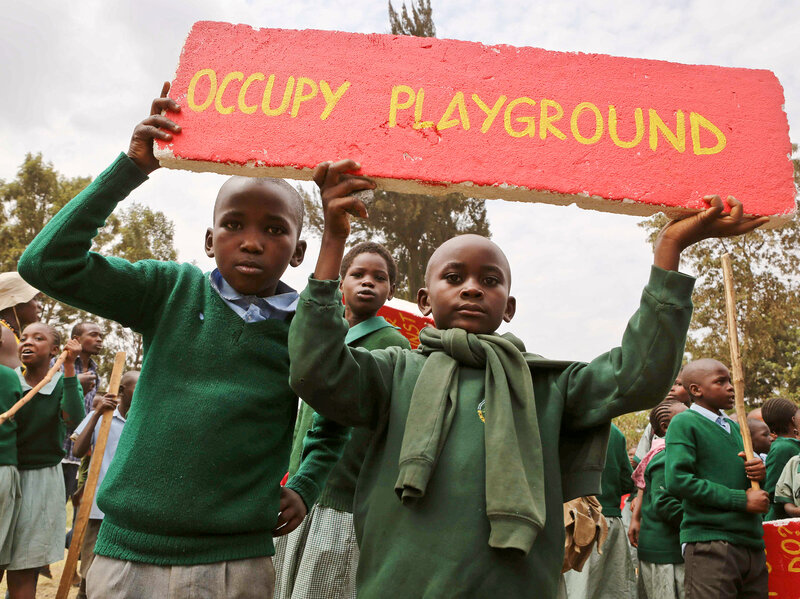 School kids hold up a sign given to them by activists at a demonstration at Langata Primary Road School.