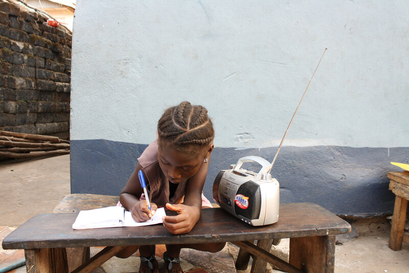 Angela Kamara, 6 years old, takes a lesson from the radio.