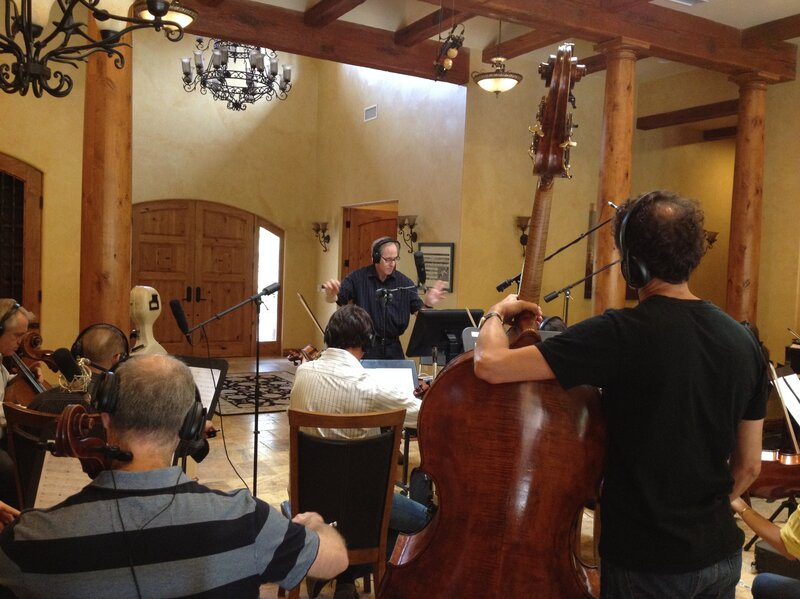 Composer Jeff Beal (center) conducts string musicians in his California home.