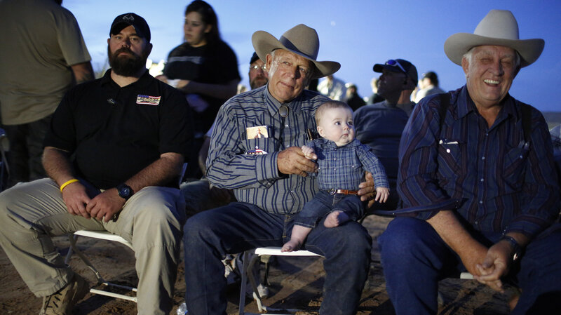 Cliven Bundy, center, holds his grandson. (AP photo by John Locher)