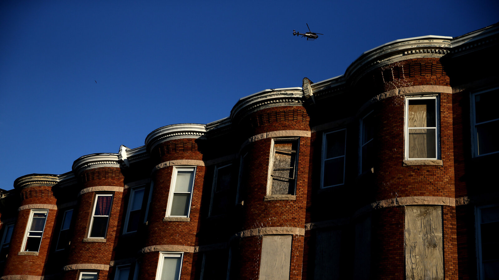"A helicopter flies over a section of Baltimore affected by riots. Richard Rothstein writes that recent unrest in Baltimore is the legacy of a century of federal, state and local policies designed to ""quarantine Baltimore's black population in isolated slums."""