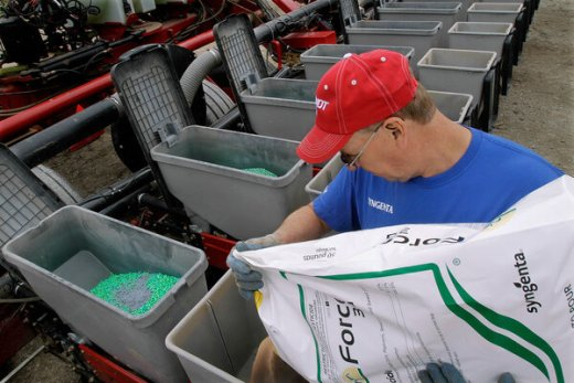 Central Illinois corn and soybean farmer Tim Seifert loads his field planter with Syngenta insecticide while planting seed corn in 2011. Monsanto has made a bid to buy Syngenta for its pesticide business.