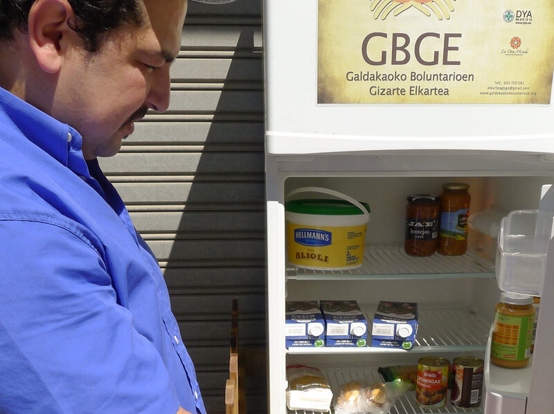 "Issam Massaoudi, an unemployed Moroccan immigrant, checks out what's inside the Solidarity Fridge. Massaoudi says money is tight for him, and it's ""amazing"" to be able to help himself to healthy food from Galdakao's communal refrigerator."