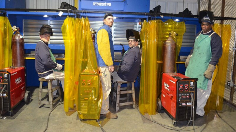 Inmates Ted Stancil (from left), Steven Bass and Christopher Peeples, with their welding Instructor Jeremy Worley (standing in center) at Walker State Prison in Georgia. The inmates are working toward a welding certificate.