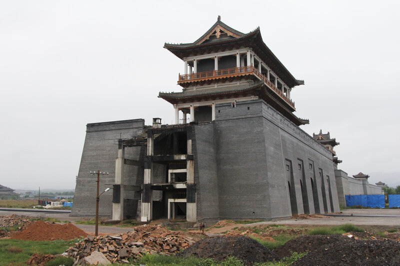 """Luliang's planned """"Liquor City"""" has run short of funding. Workers have yet to finish this replica of the Great Wall, which is supposed to surround a massive factory complex producing baijiu, an often expensive Chinese hard liquor."""